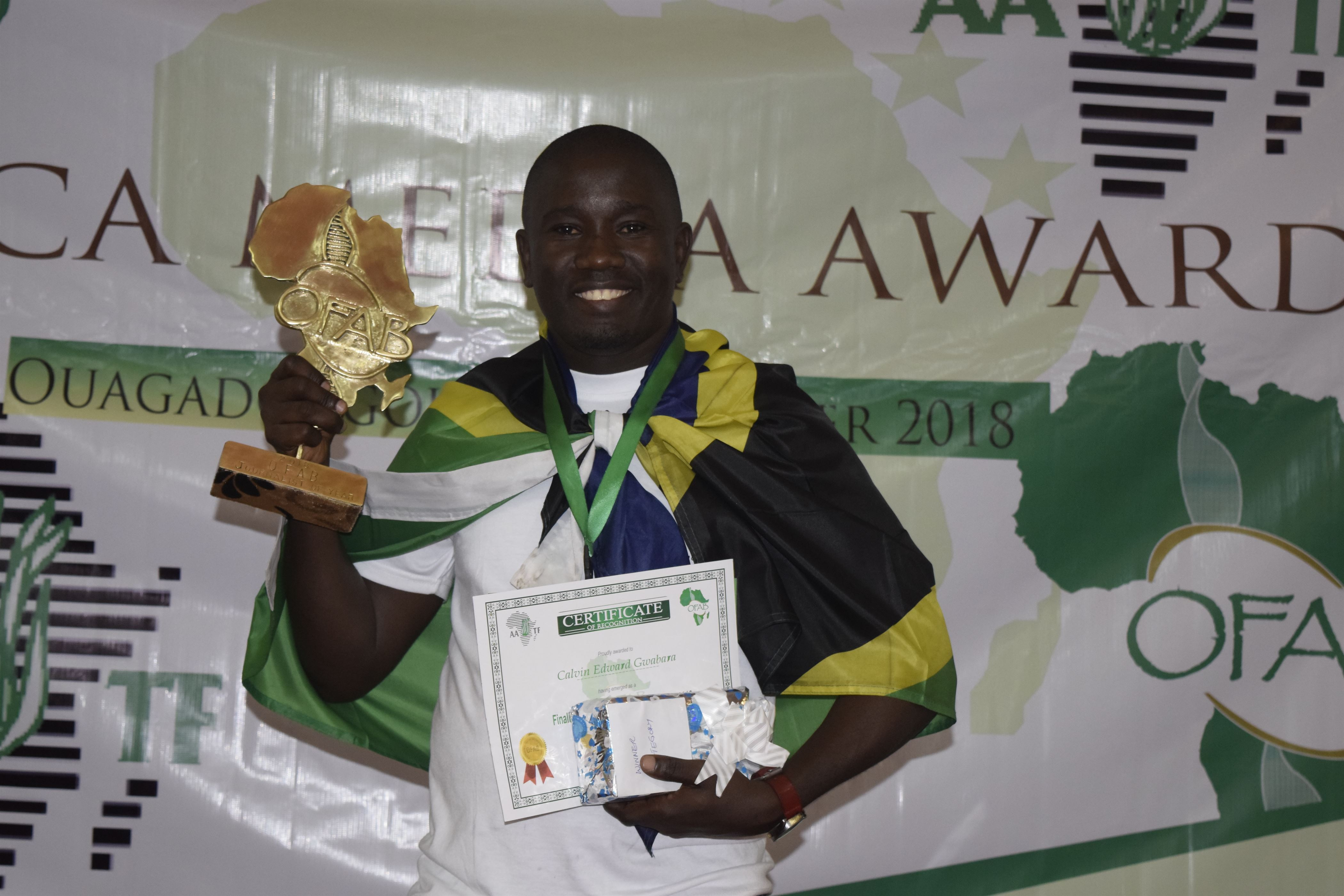 Mr Calvin Gwabara Displaying Awards and Certificates after emerged the winner of the Open Forum on Agriculture Biotechnology (OFAB) Africa Media Awards, 2018.