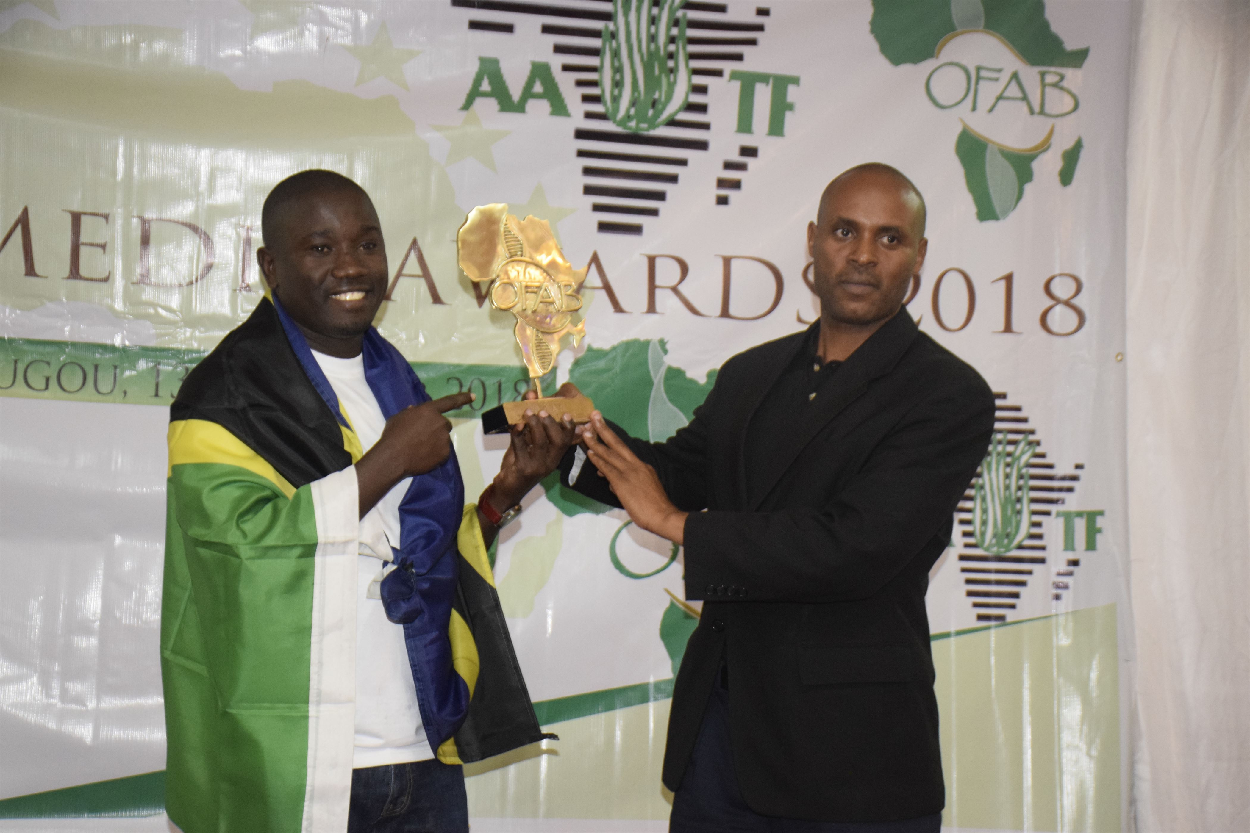 Tanzania OFAB Country cordinator Dr. Philbert Nyinondi taking a photo with winner