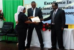SUAMEDIA correspondent Farida Mkongwe (left) receiving prizes on behalf of Calvin Gwabara of SUAMEDIA from the permanent secretary in the Ministry of Education, Science and Technology Dr. Leornad Akwilapo(Right). Witnessing is the acting Director General of the Tanzania Commission for Science and Technology (COSTECH) Dr. Amos Nungu